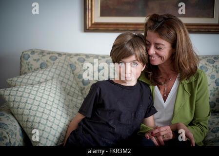 Caucasian grandmother and grandson sitting on sofa