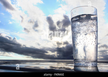 Ice cold glass of water with dramatic cloudy sunset - Stock Photo