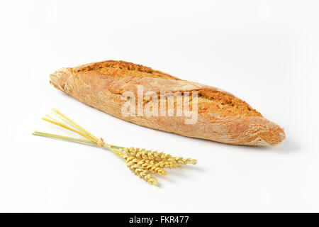 freshly baked french baguette and bunch of ripe ears on white background - Stock Photo