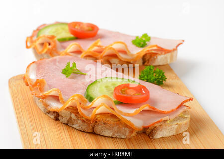 close up of two open faced ham sandwiches on wooden cutting board - Stock Photo