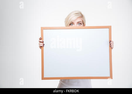 Blonde woman peeking from blank board isolated on a white background - Stock Photo