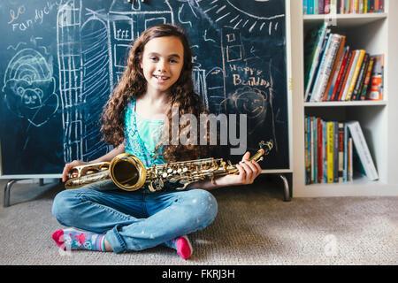Mixed race girl holding saxophone on floor Stock Photo