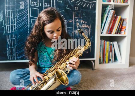 Mixed race girl playing saxophone on floor Stock Photo