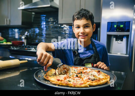 Mixed race boy slicing pizza in kitchen - Stock Photo