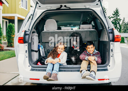 Mixed race children sitting with dog in car hatch - Stock Photo
