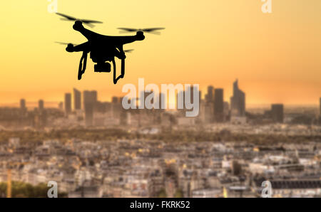 Drone silhouette flying above Paris city panorama - Stock Photo
