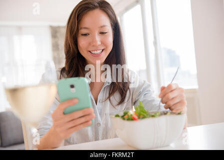 Mixed race woman photographing salad - Stock Photo