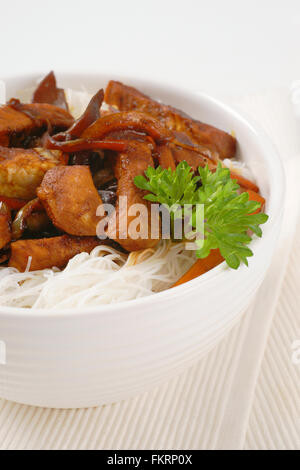 bowl of roasted meat, ear mushrooms and rice noodles on white place mat - Stock Photo