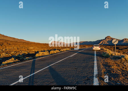 Tarmac road goes through a huge lava field in the foot of Teide volcano (Tenerife island). - Stock Photo