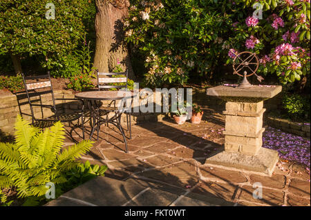 Table, chairs and stone sundial, on patio in summer sun - beautiful, traditional, landscaped garden, Burley-in-Wharfedale, - Stock Photo