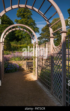 View along a tunnel arbour to flowering plants on raised border - beautiful designed & landscaped, traditional garden - Stock Photo