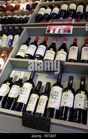 Bottles of wine on Sale and displayed on shelves. - Stock Photo
