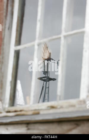 Old windmill reflection through window - Stock Photo