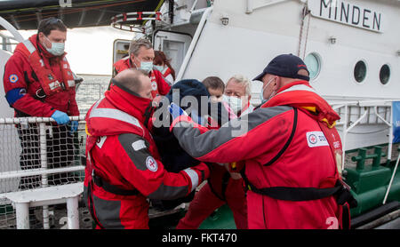 Mytilini, Greece. 10th Mar, 2016. Marco Behns (L) and foreman Ulrich Fader carry a rescued baby from Afghanistan - Stock Photo