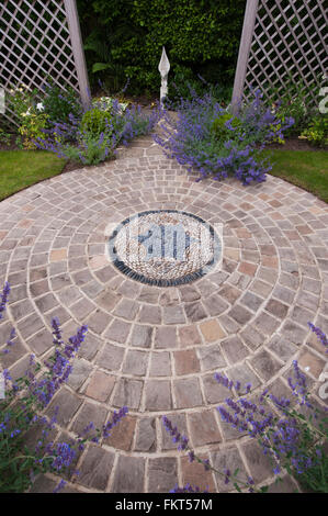 Cobble mosaic, decorative stone paving, plants, sculpture and trellis in designed, landscaped, garden, Burley-in - Stock Photo