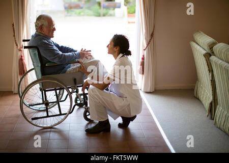 Nurse talking to patient in wheelchair - Stock Photo