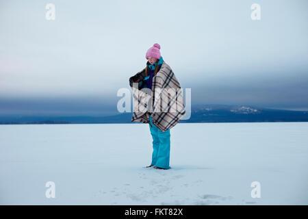 Caucasian teenage girl wrapped in blanket in snow