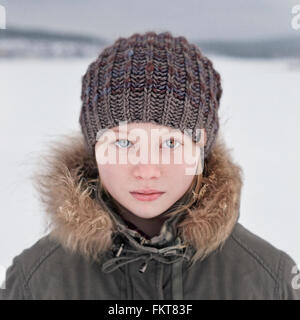 Caucasian teenage girl wearing beanie hat in snow - Stock Photo