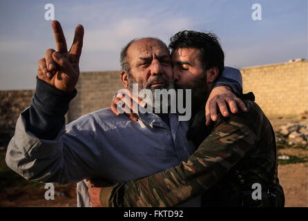 SYRIA. MARCH 10, 2016. Abu Juma (R), a commander of a Jaysh al-Thuwar unit, hugs his unidentified fellow fighter - Stock Photo