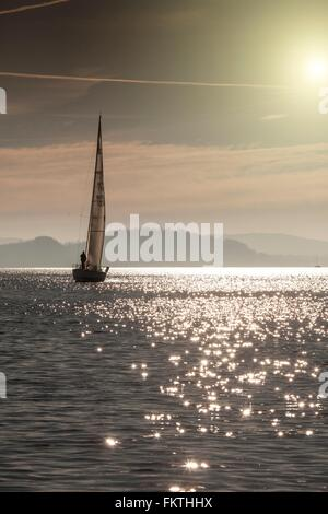Boat on sparkling water surface, Lake Maggiore, Piedmont, Lombardy, Italy - Stock Photo