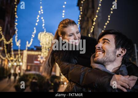 Young man giving young woman piggyback face to face smiling - Stock Photo