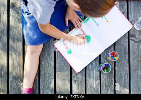 Girl drawing picture in notebook, high angle - Stock Photo