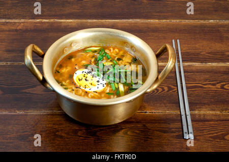 Korean ramen with egg and green onion on golden pan - Stock Photo