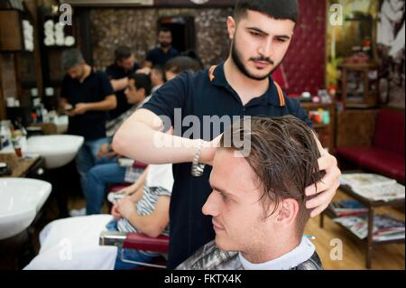 Hairdresser in barbershop cutting young mans hair - Stock Photo