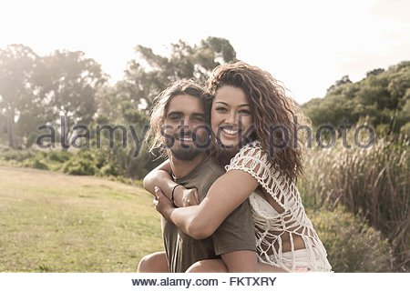 Young man giving young woman piggyback looking at camera smiling - Stock Photo