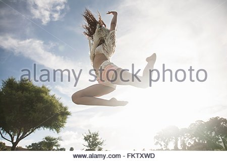 Low angle view of young woman jumping in mid air, arms raised - Stock Photo