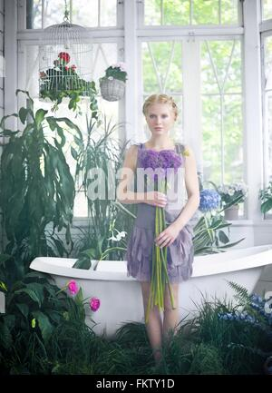 Young woman holding bouquet of flowers, standing in bathroom filled with plants - Stock Photo