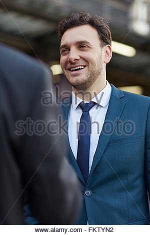 Businessman wearing suit talking to colleague smiling - Stock Photo