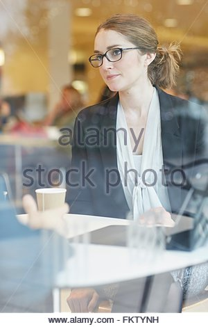View through window of businesswoman wearing eye glasses sitting at table looking at colleague - Stock Photo