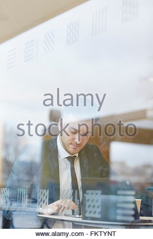 View through window of businessman sitting at table texting, looking down - Stock Photo