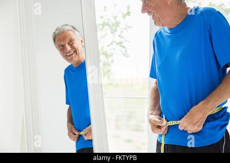 Happy senior man measuring his waist whilst looking in mirror - Stock Photo
