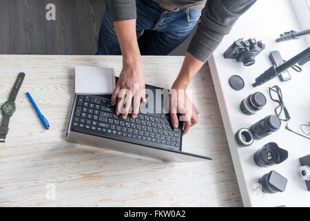 Overhead view of male photographer typing on studio desk laptop - Stock Photo