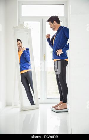 Happy mature man weighing himself whilst looking in mirror at home - Stock Photo