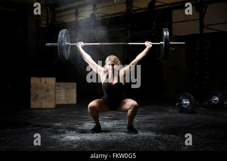Young woman weightlifting barbell in dark gym - Stock Photo
