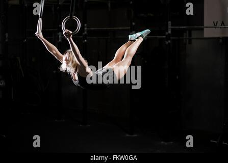 Young woman swinging on gym rings in dark gym - Stock Photo