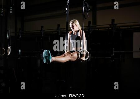 Young woman poised on gym rings in dark gym - Stock Photo