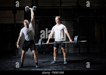 Two young men weightlifting with dumbbell and barbell in dark gym - Stock Photo