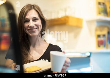Portrait of young female waitress holding coffee and cake in cafe - Stock Photo