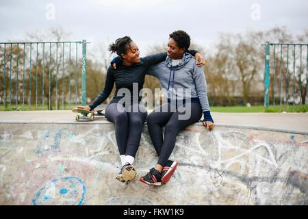 Two young female skateboarding friends sitting in skateboard park - Stock Photo