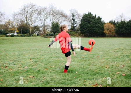 Teenage female soccer player practicing keepy uppy in park - Stock Photo