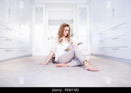 Young woman sitting on floor reading a book in bedroom - Stock Photo