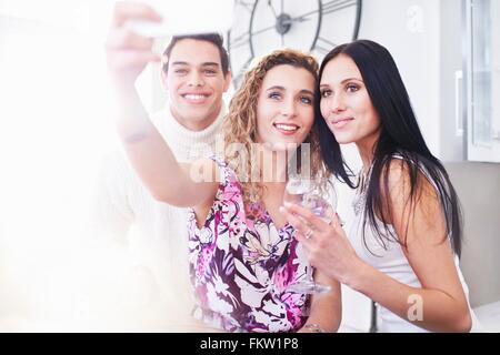Three young adult friends posing for smartphone selfie in kitchen