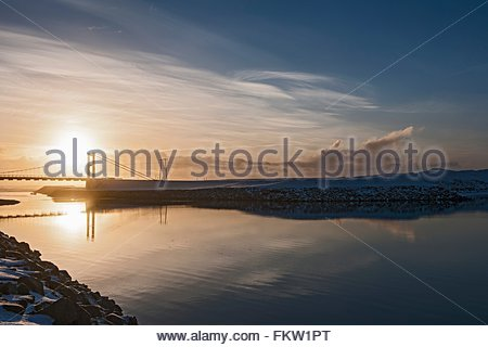 Silhouetted view of bridge at midday in January at the glacier Lagoon Jokulsa Loni, East Iceland - Stock Photo