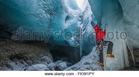 Ice climber climbing up ice cave below the Gigjokull glacier, Thorsmork, Iceland - Stock Photo