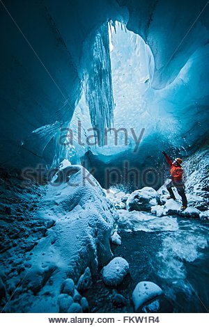 Man looking up from ice cave below the Gigjokull glacier, Thorsmork, Iceland - Stock Photo