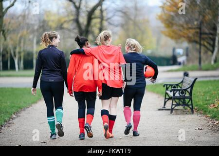 Rear view of female soccer players en route to play soccer in park - Stock Photo